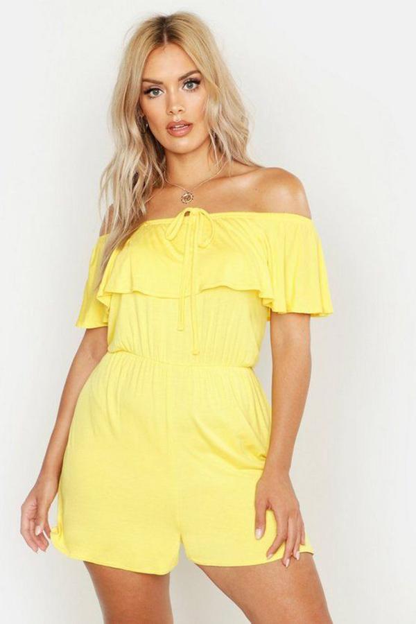 A plus-size model wearing a yellow romper.