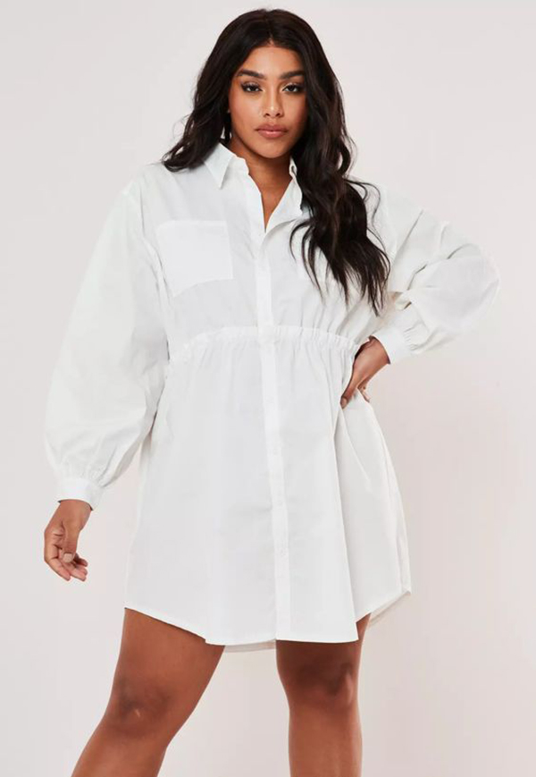 A plus-size model wearing a white mini shirtdress.