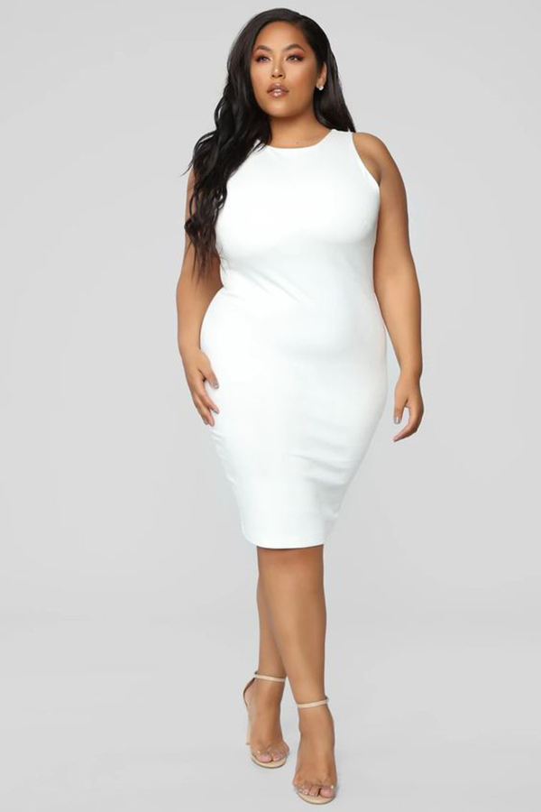 A plus-size model wearing a figure-hugging white dress.