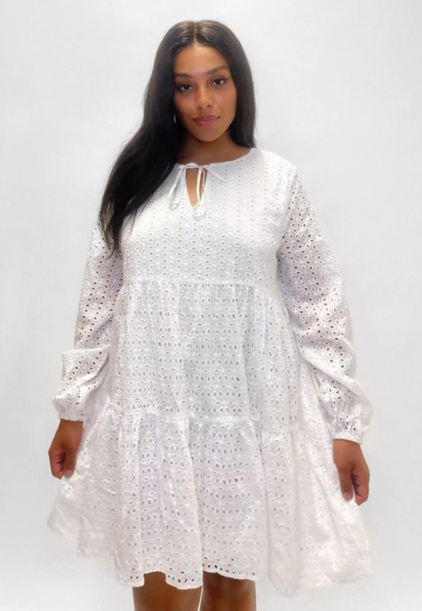A plus-size model wearing a white lace smock dress.