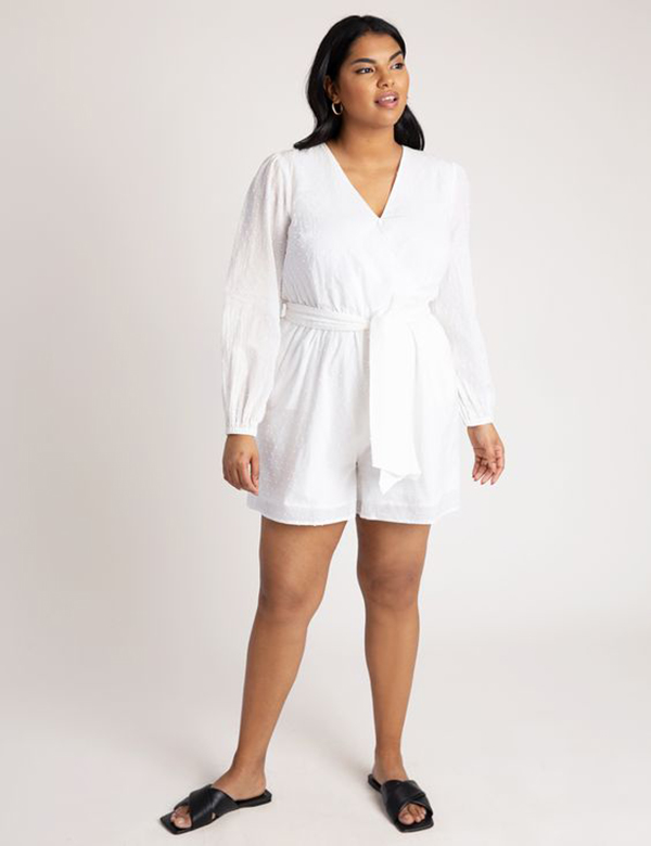 A plus-size model wearing a white romper.