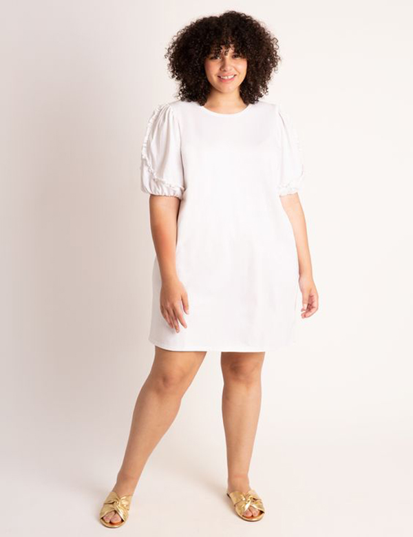 A plus-size model wearing a white dress.