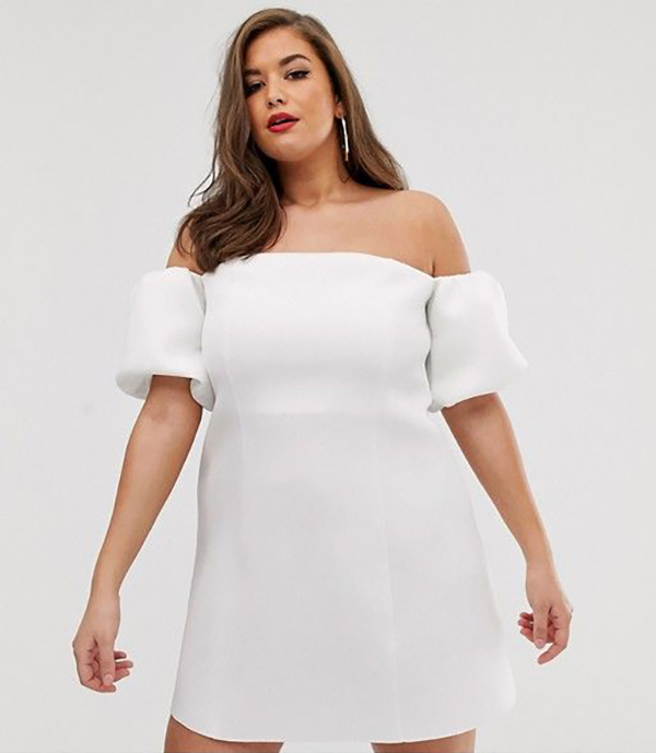 A plus-size model wearing a white mini dress.
