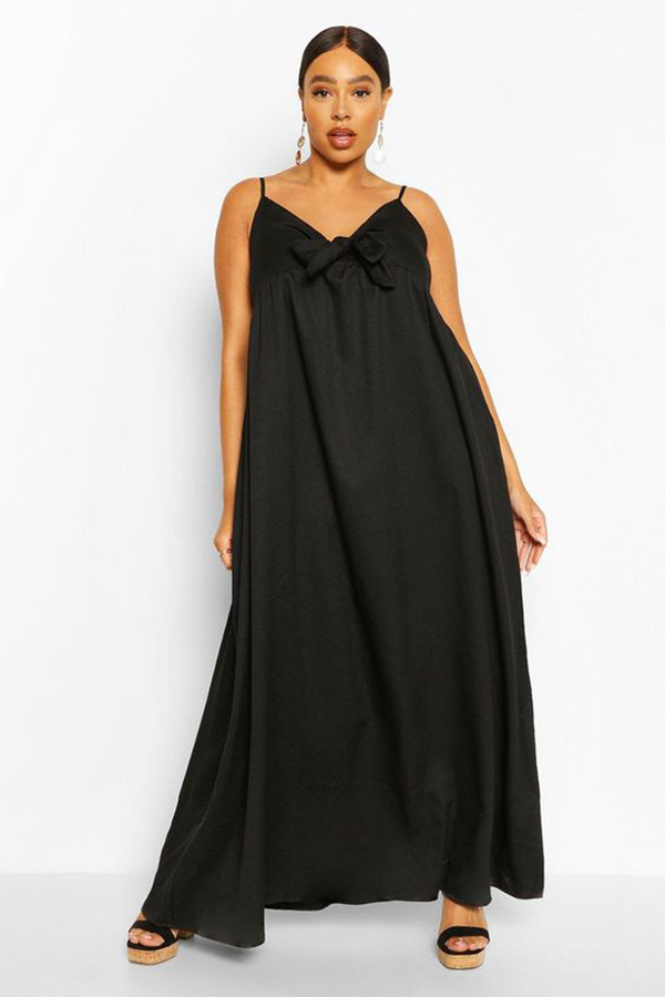 A plus-size model wearing a black maxi dress.