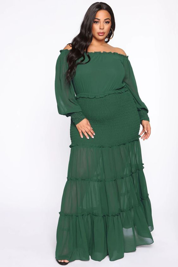A plus-size model wearing a green off-the-shoulder maxi dress.