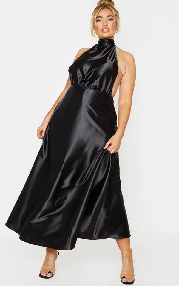 A plus-size model wearing a silky black dress.