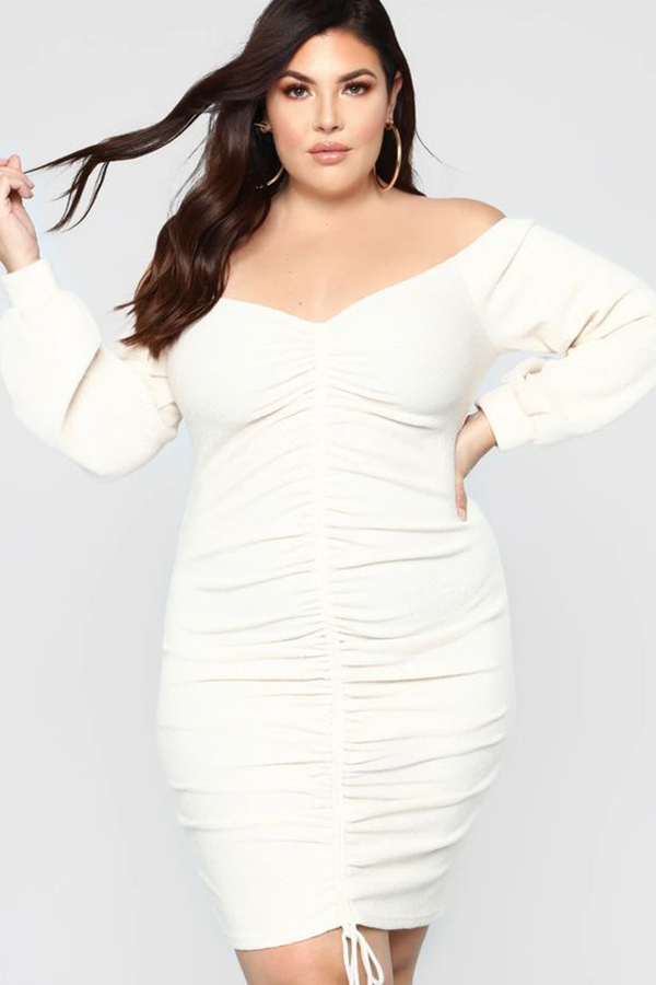 A plus-size model wearing a white ruched dress.