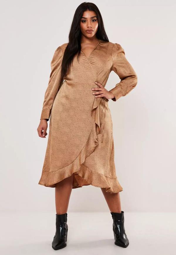 A plus-size model wearing a gold wrap dress.