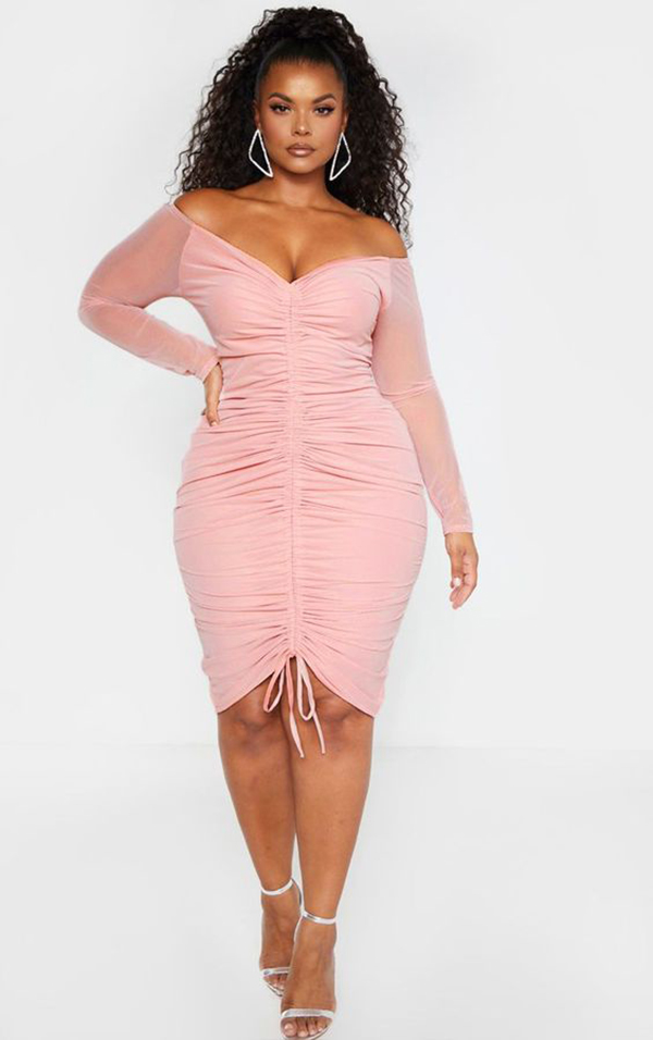 A plus-size model wearing a pink ruched dress.