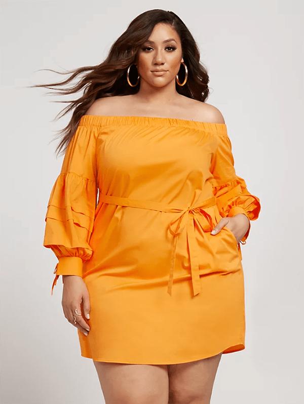 A plus-size model wearing an orange off-the-shoulder dress.