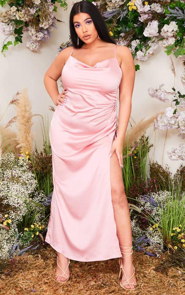A plus-size model wearing a pink slip dress.
