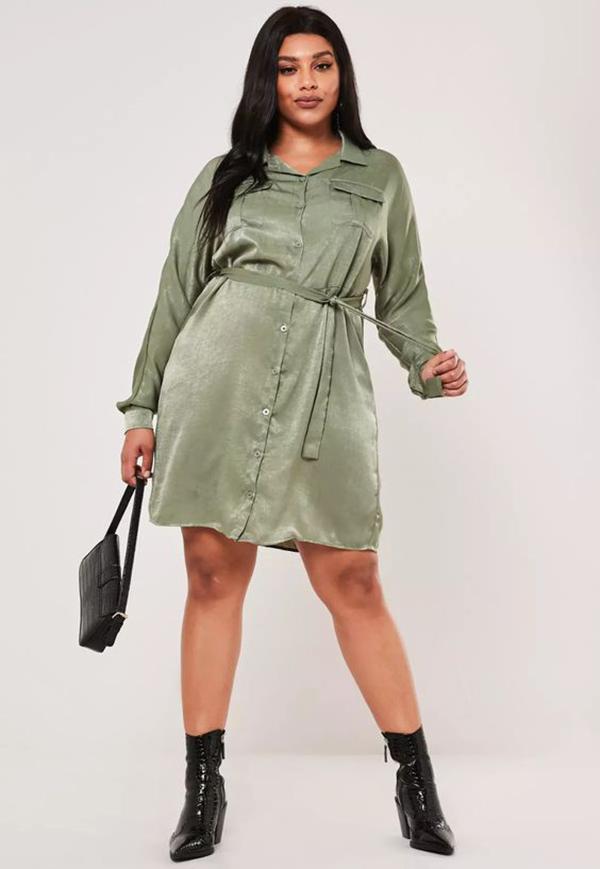 A plus-size model wearing an aqua shirt dress.