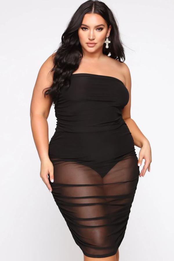 A plus-size model wearing a strapless black dress.