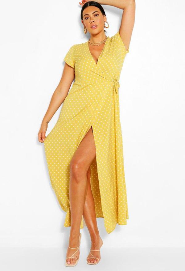A plus-size model wearing a yellow wrap dress.