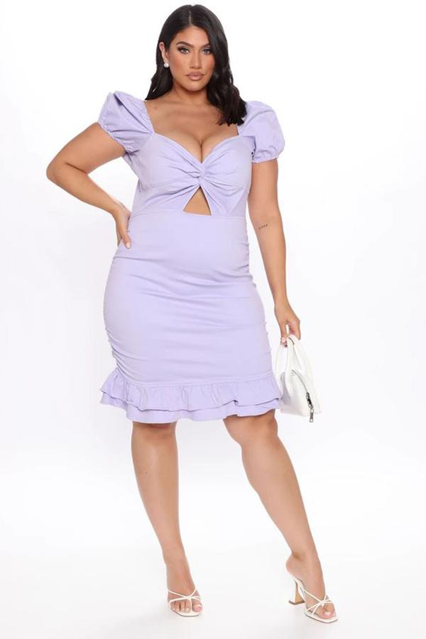 A plus-size model wearing a purple midi dress.
