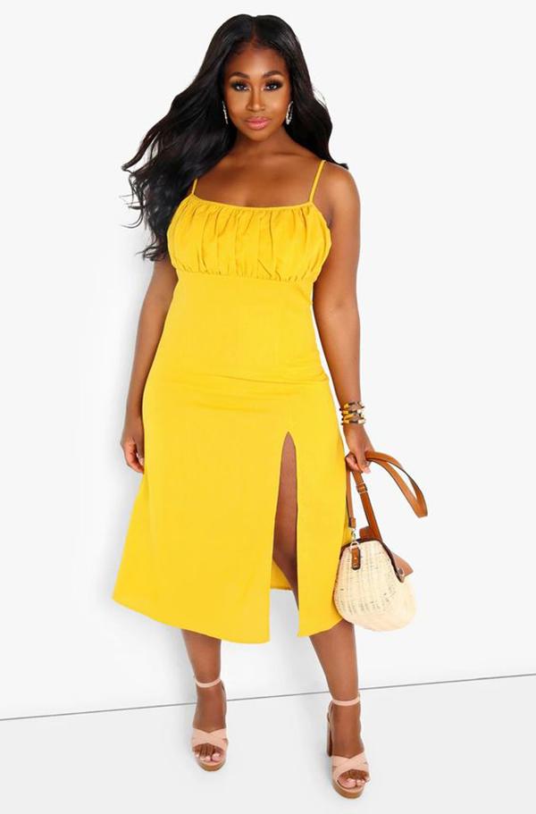 A plus-size model wearing a yellow midi dress.