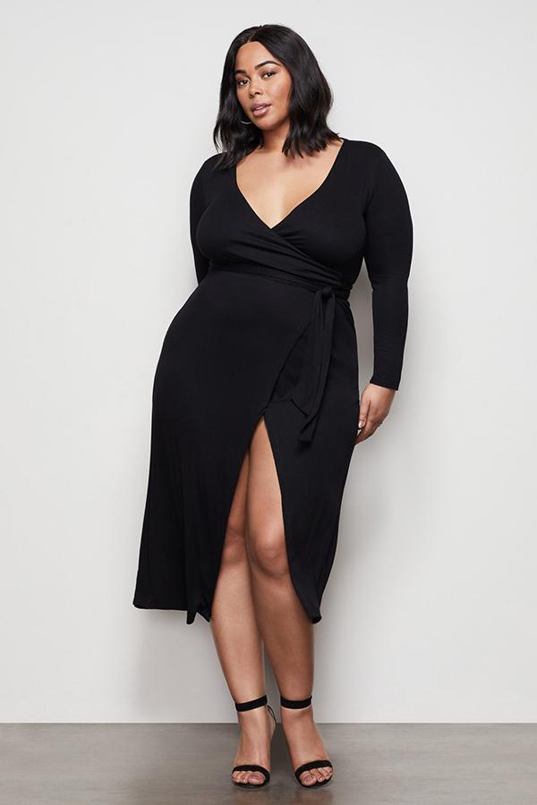 A plus-size model wearing a black wrap dress.