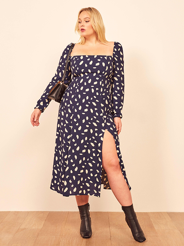A plus-size model wearing a navy printed dress.