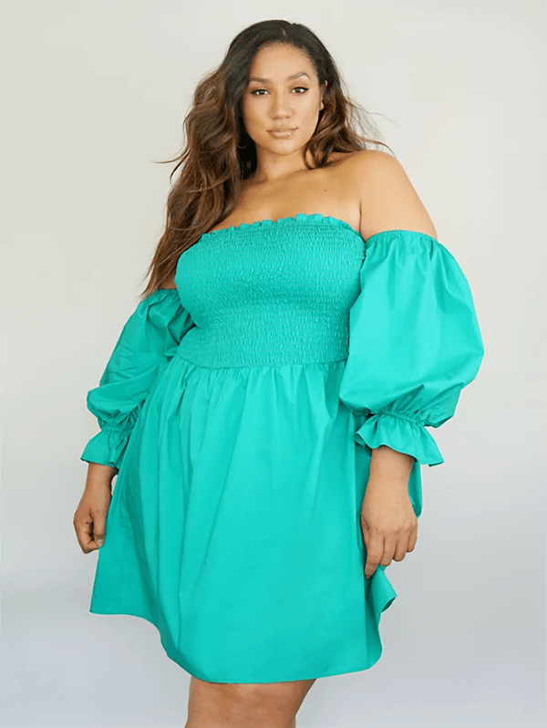 A plus-size model wearing a green off-the-shoulder dress.