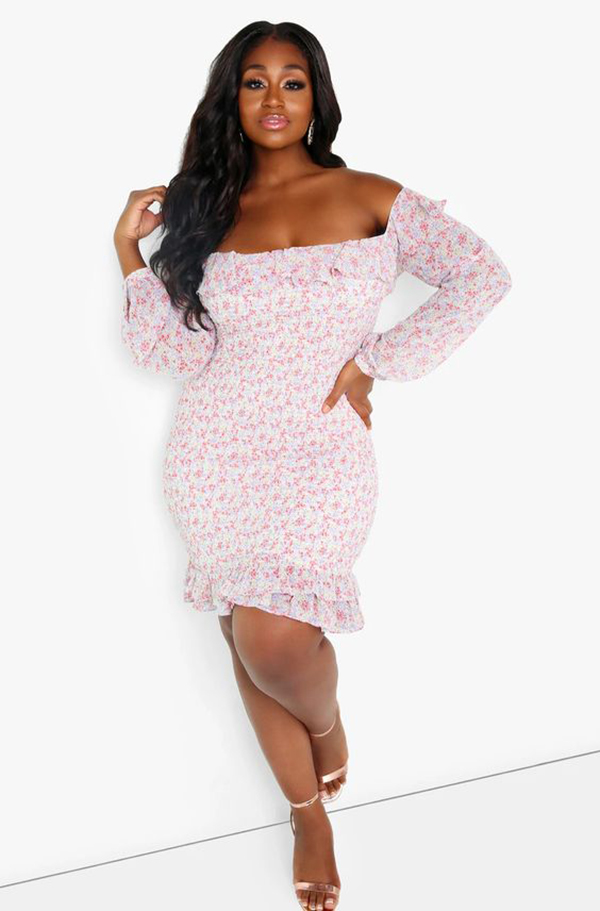 A plus-size model wearing an off-the-shoulder dress.