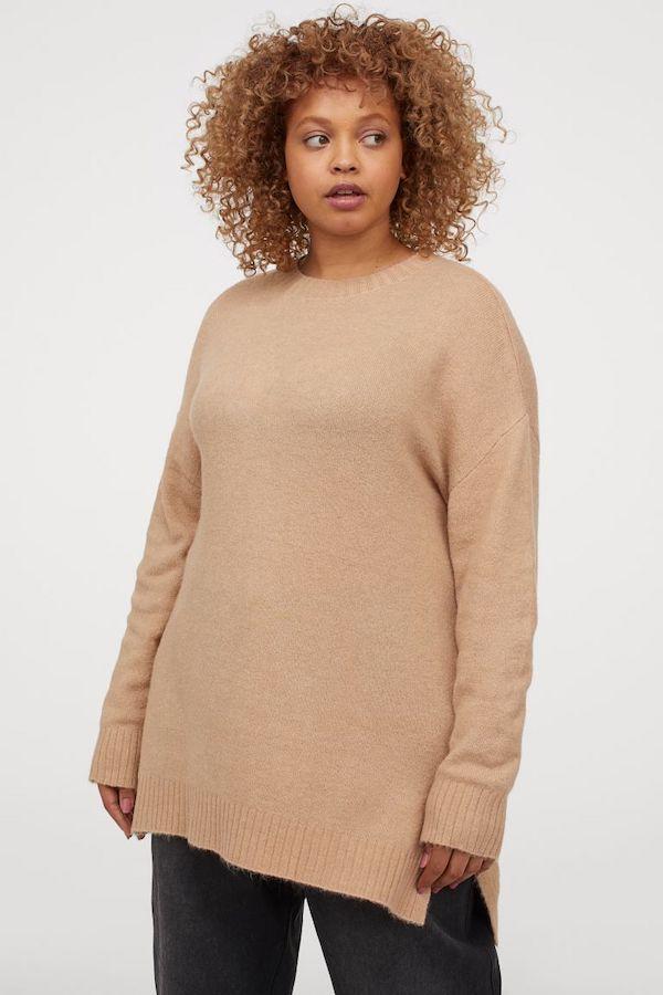 A model wearing a plus-size oversized sweater in tan.