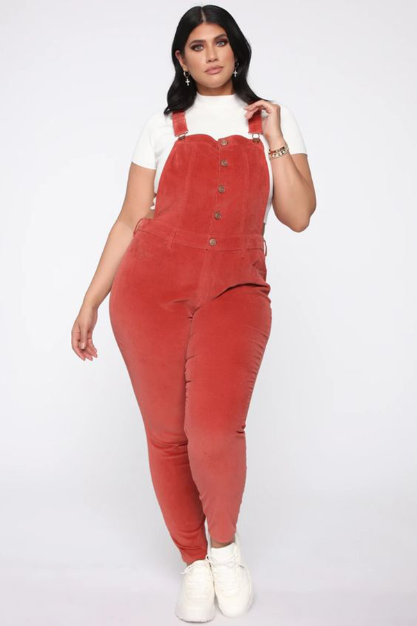 A plus-size model wearing corduroy overalls.
