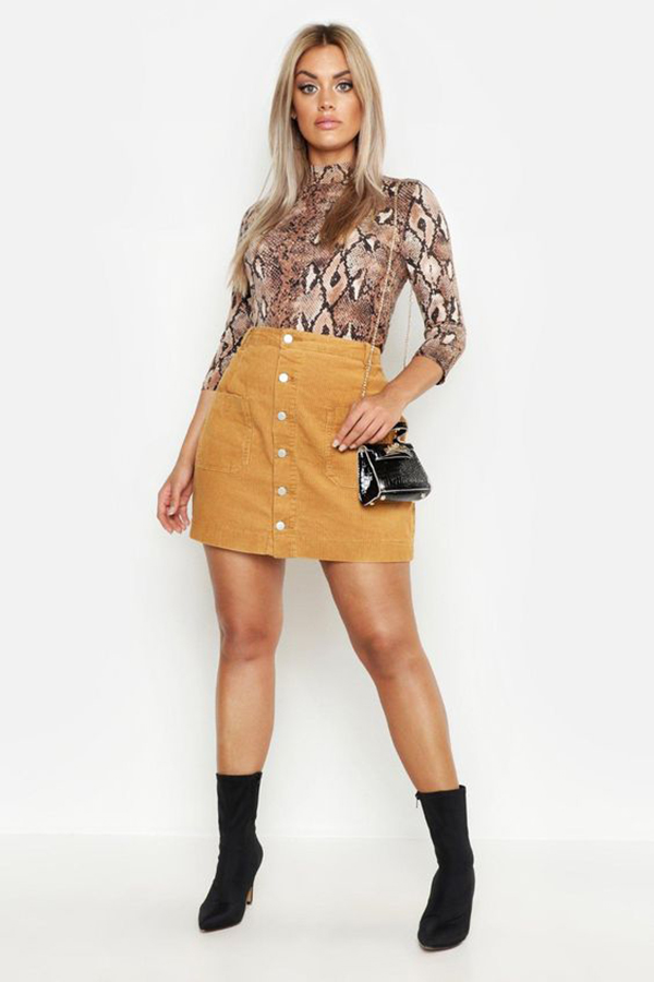 A plus-size model wearing a corduroy mini skirt.