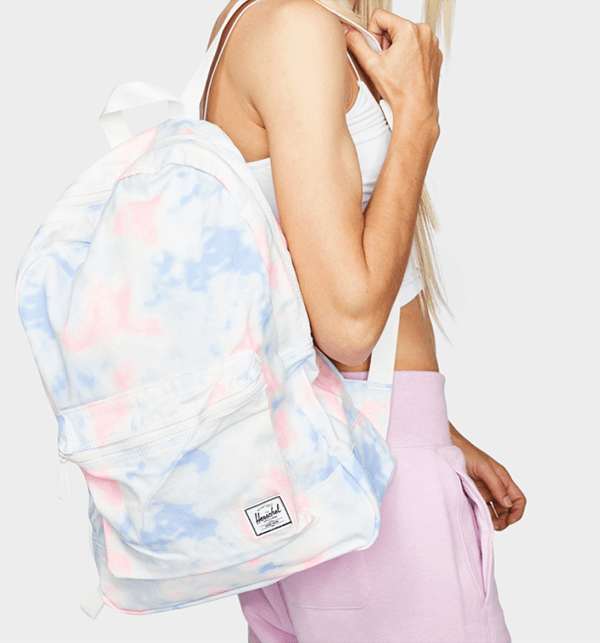 A model carrying a pastel tie-dye backpack.