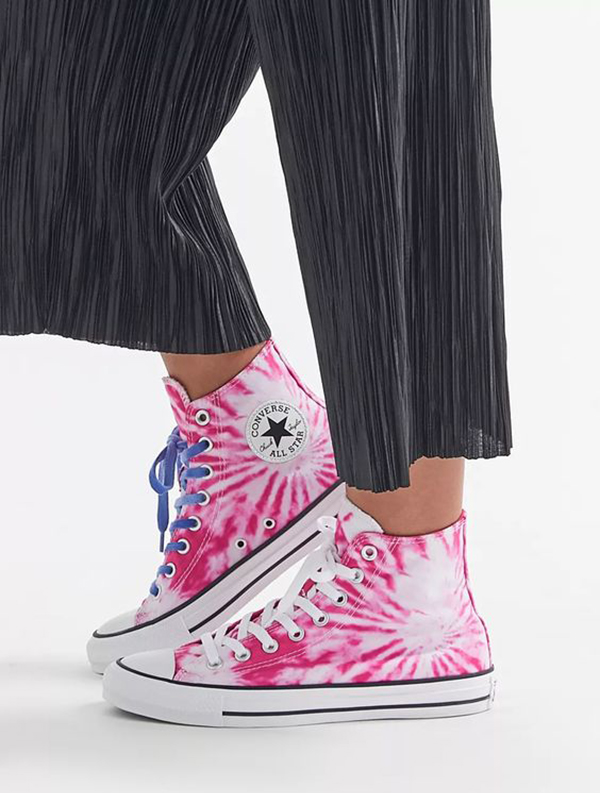 A pair of legs wearing hot pink tie-dye high-top sneakers.