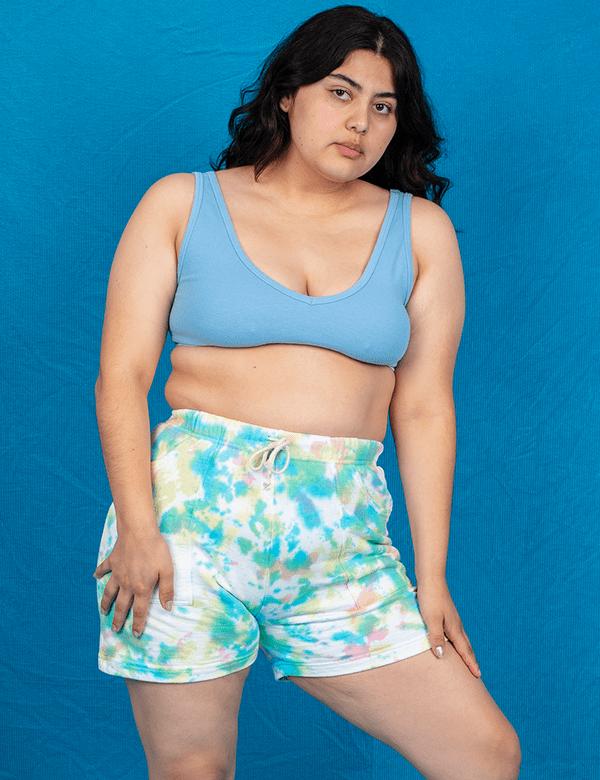 A plus-size model wearing tie-dye sweat shorts.
