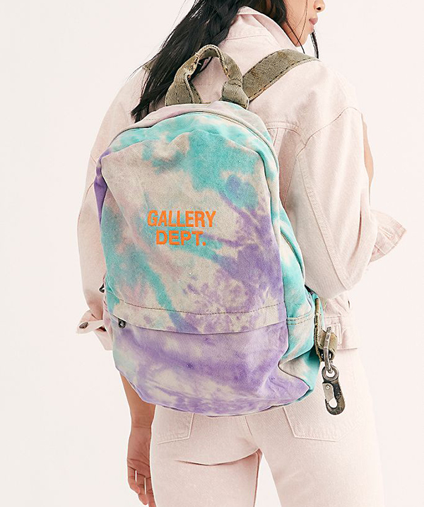 A model carrying a tie-dye backpack.