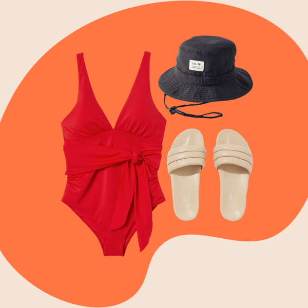 red one-piece swimsuit, black bucket hat, tan slide sandals