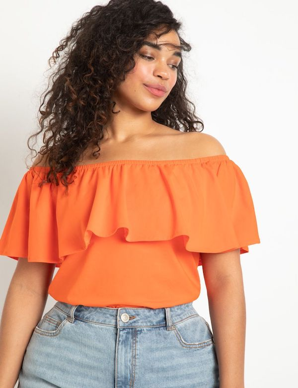 A model wearing a plus-size off-the-shoulder top.