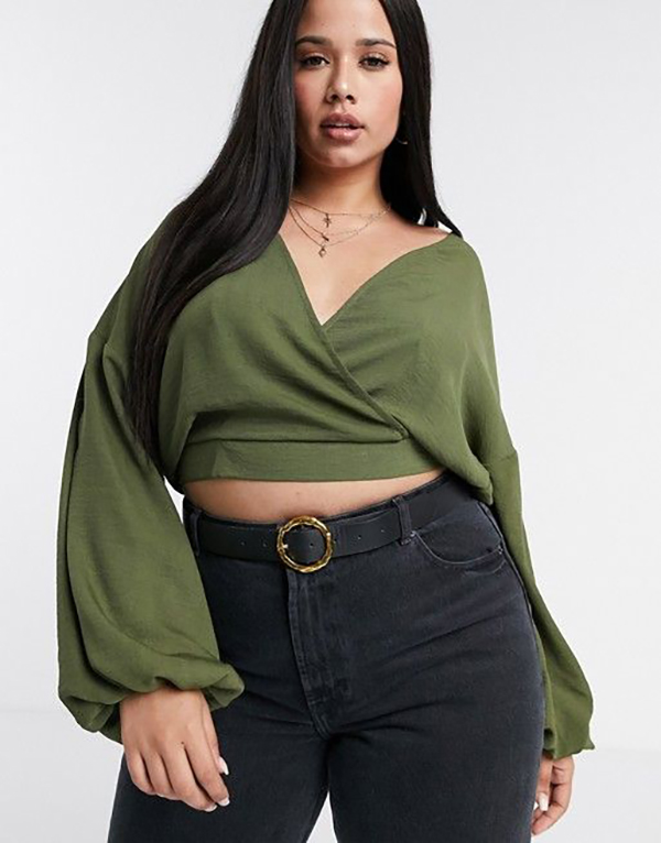 A plus-size model wearing a long-sleeve olive green crop top.