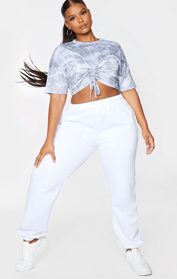 A plus-size model wearing a gray tie-dye crop top.