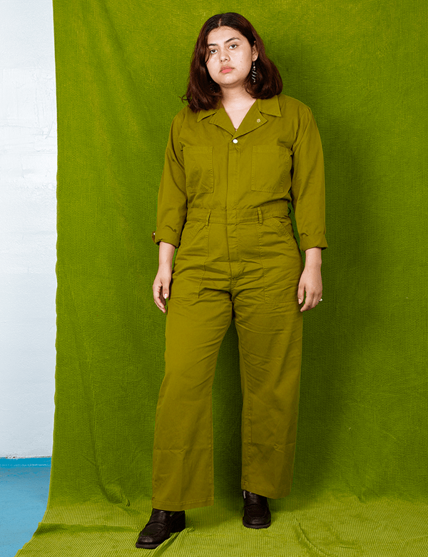 A plus-size model wearing an olive green utility jumpsuit.