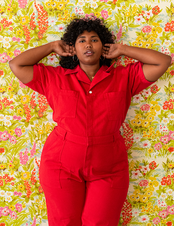 A plus-size model wearing a red utility jumpsuit.