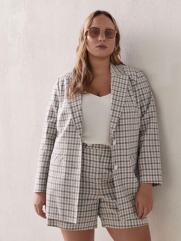 A woman wearing a gray plaid blazer.