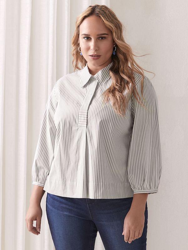 A woman wearing a striped blouse.