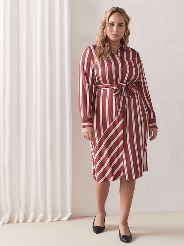 A woman wearing a red and white striped shirtdress.