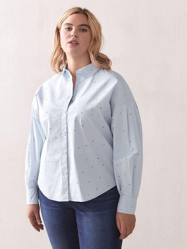 A woman wearing a blue button down shirt.
