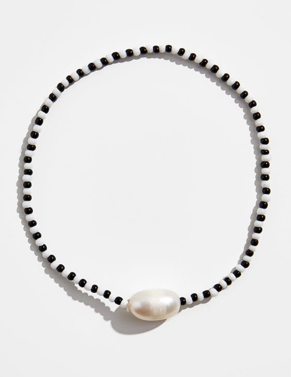 Black and white beaded bracelet with a pearl on it.