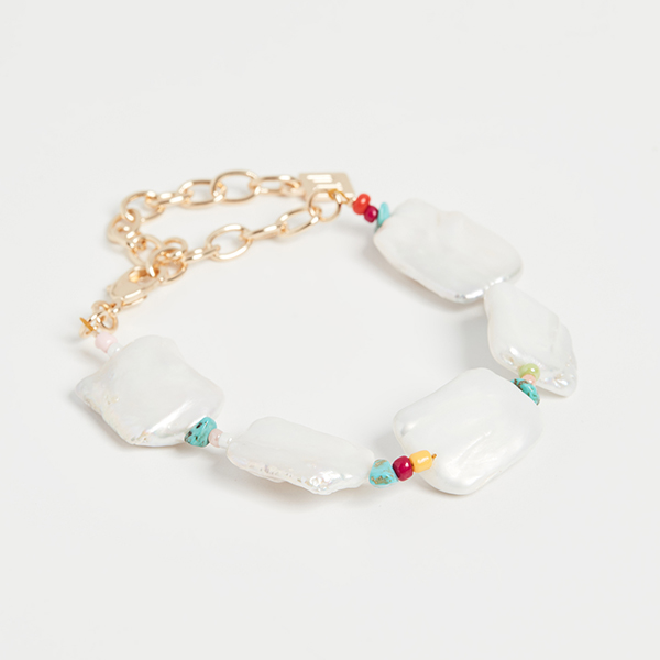 A gold chain bracelet with large rectangular pearls and red and aqua beads.