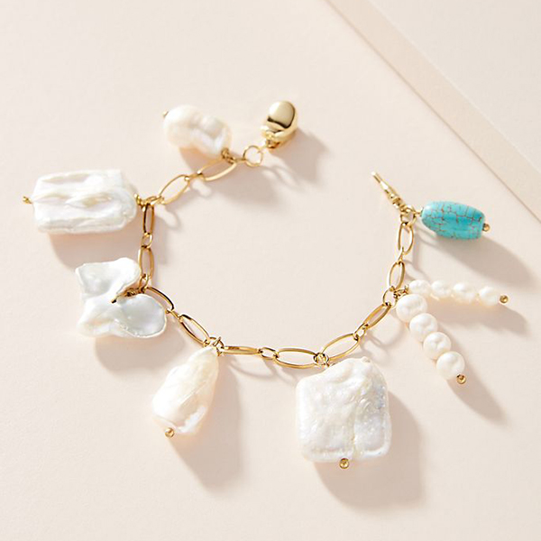 A charm bracelet with large misshapen pearls dangling from it.