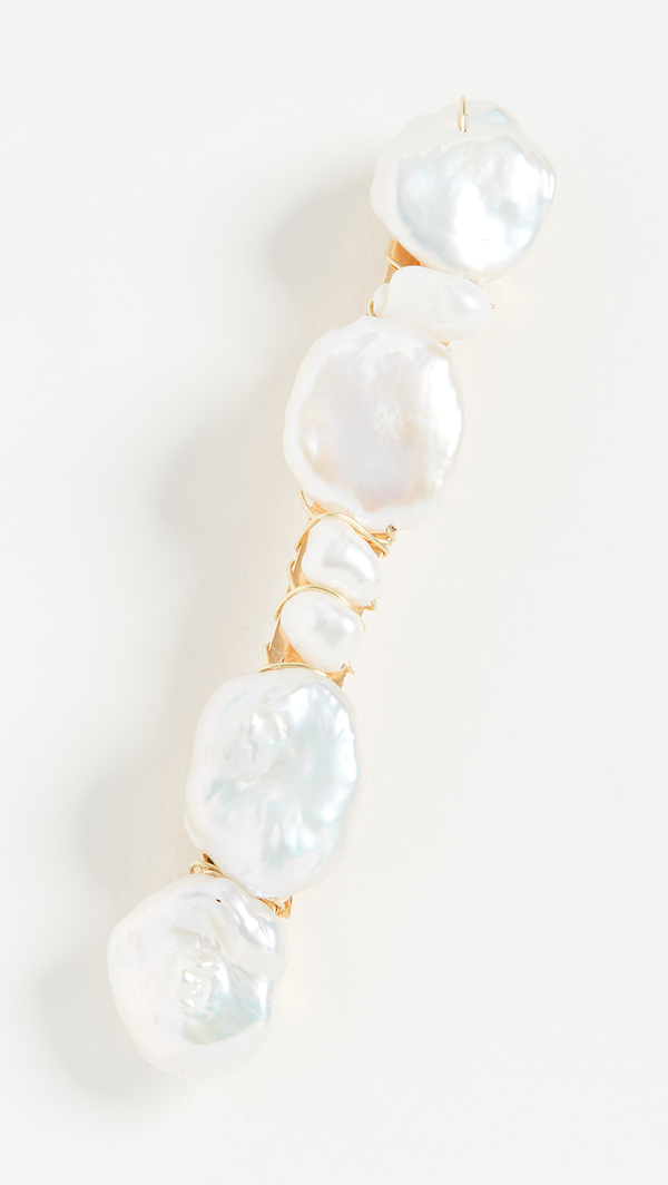 A barrette covered in pearls of different shapes and sizes.