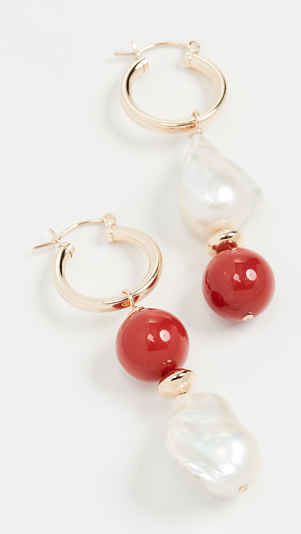 A pair of asymmetrical drop earrings featuring large red beads and large pearls.