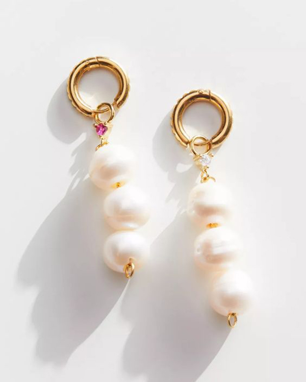 A pair of pearl drop earrings on small gold hoops.