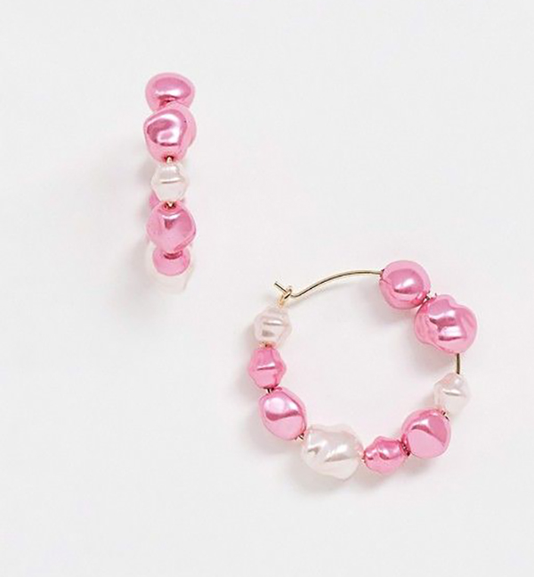A pair of hoop earrings covered in hot pink pearls.
