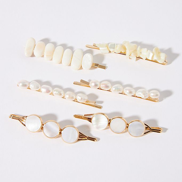 A set of bobby pins covered in pearls and pearl pieces.