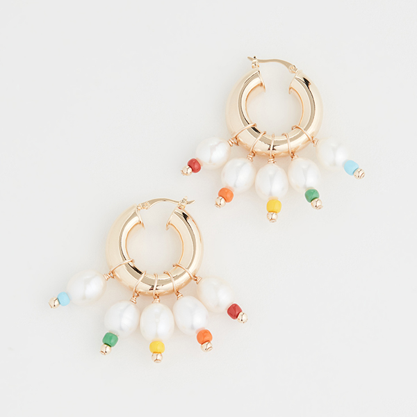 A pair of small gold hoop earrings with pearls and rainbow beads dangling from it.